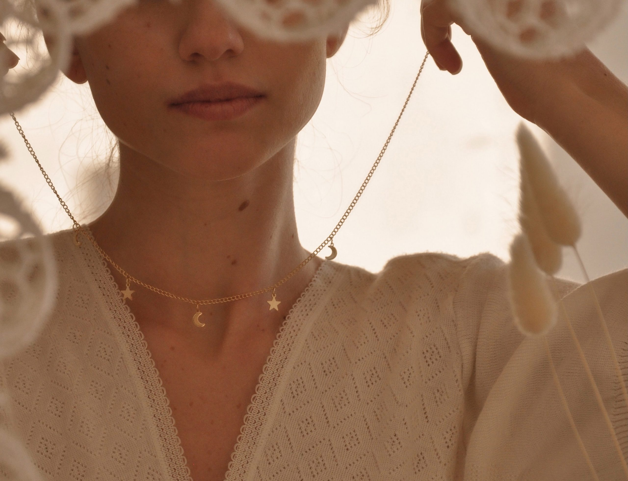 Woman putting on gold necklace