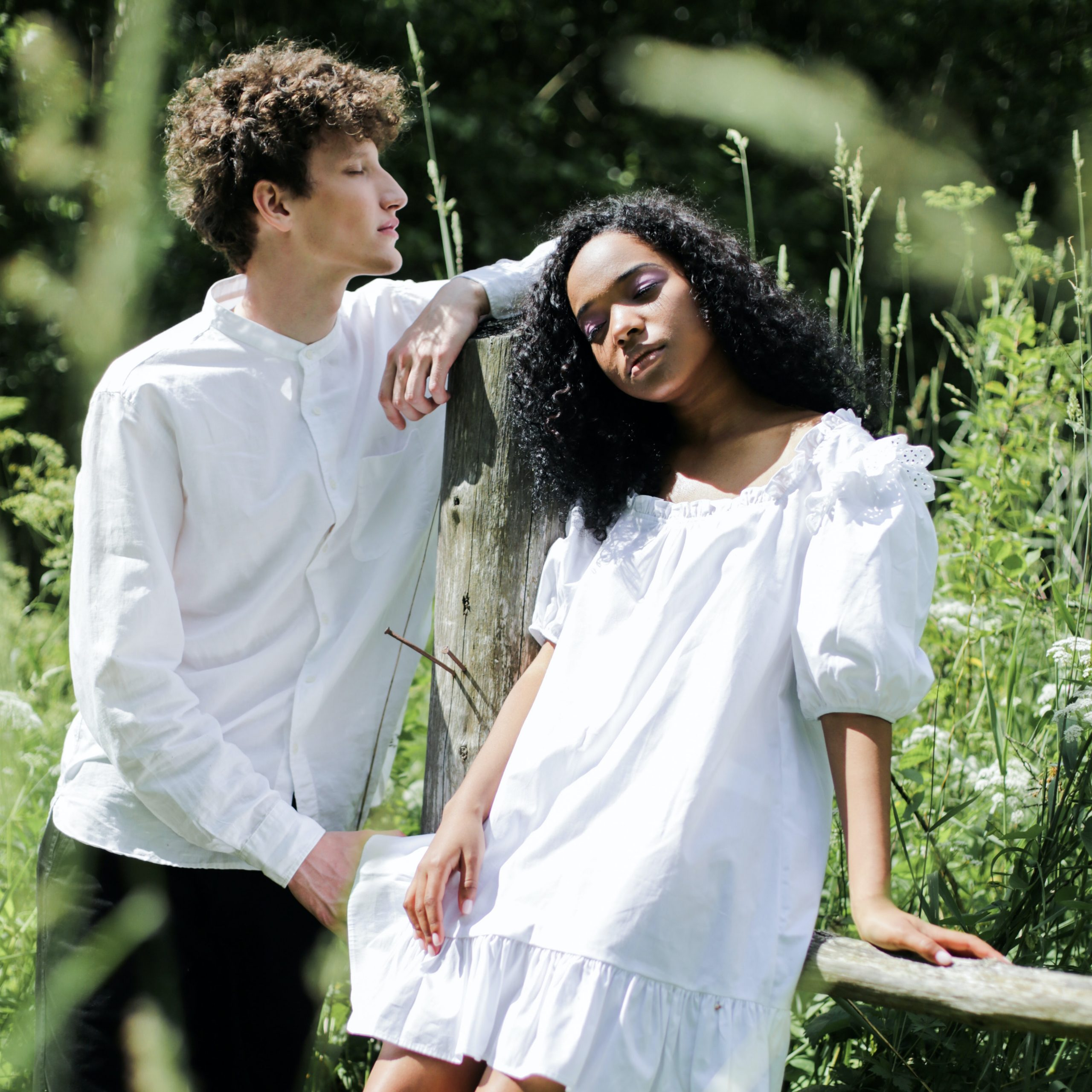 2 people in front of greenery