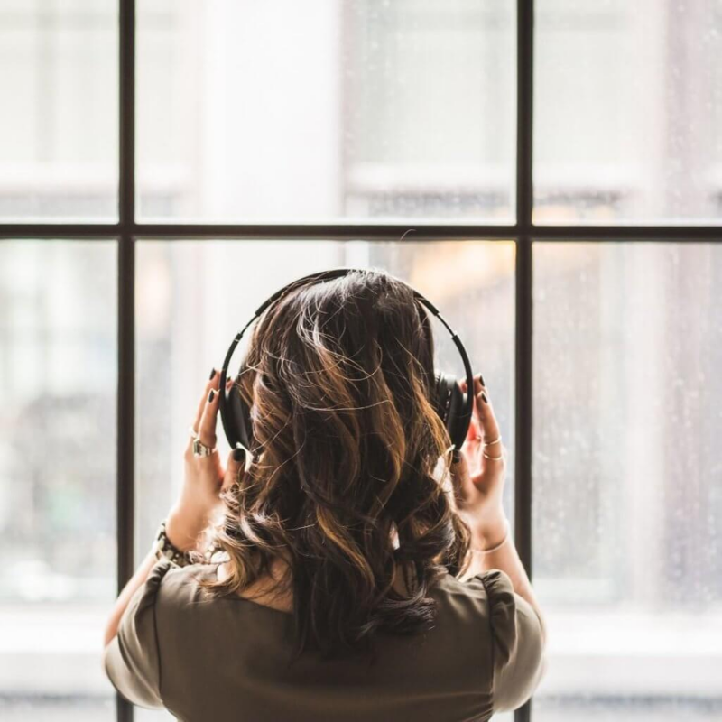 Woman listening to song through headphones