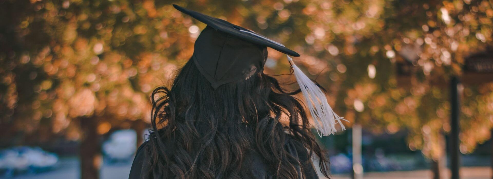 Girl walking with graduation cap and gown
