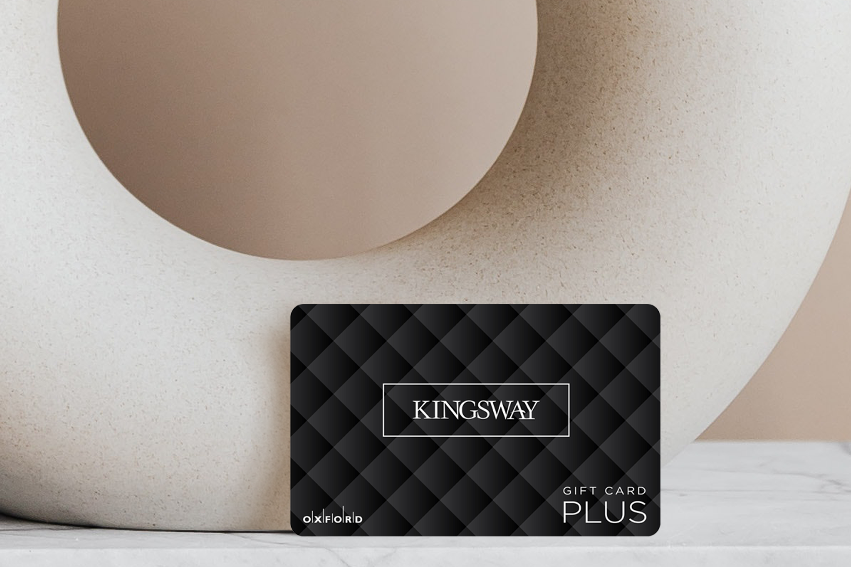 Kingsway black quilted gift card leaning against beige circular vase with a taupe wall.