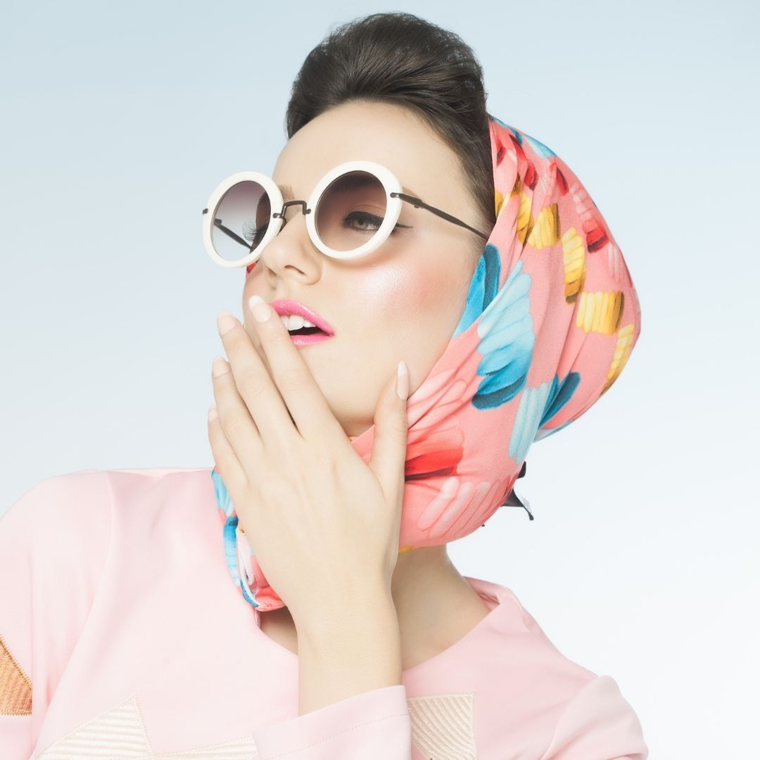 Woman in a silk scarf and round glasses