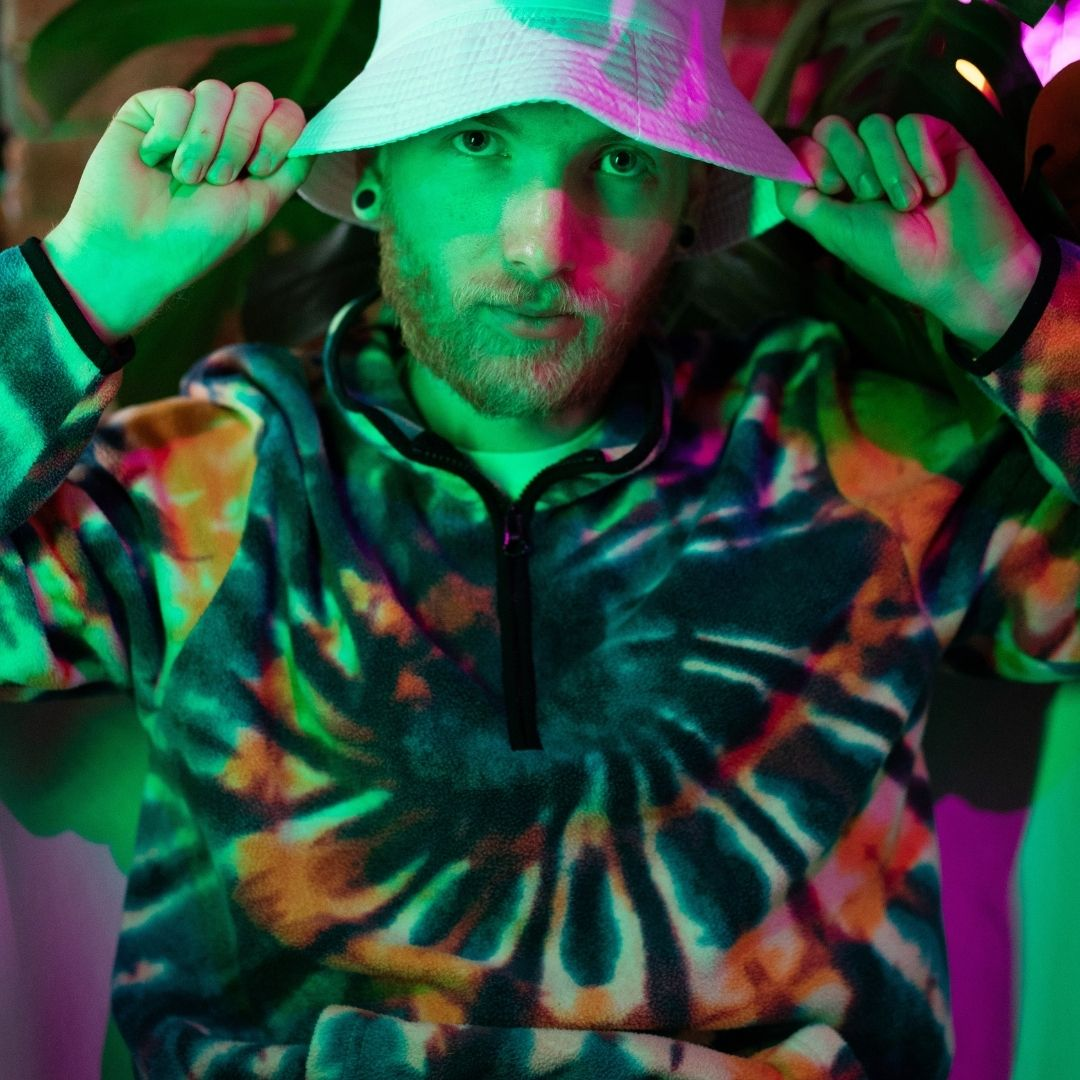 Man in a tie dye hoodie and white hat